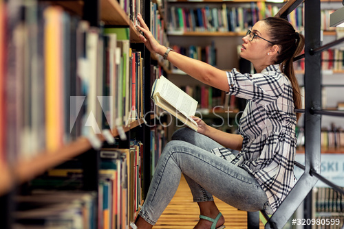 woman sitting picking book out in library
